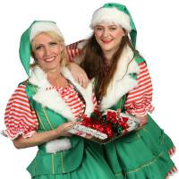 2 Kerstvrouwtjes delen kerstkransjes uit