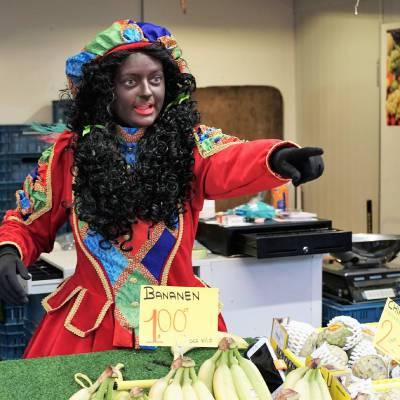 Twee Zwarte Pieten delen uit - 1000 Taai-Taai popjes inzetten?