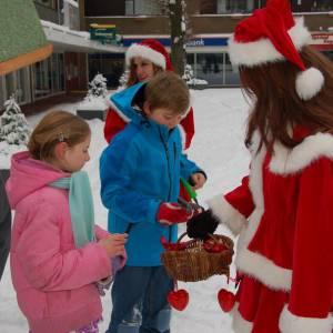 Kerstman en Kerstvrouwtje delen Kerstkransjes uit boeken of inzetten?